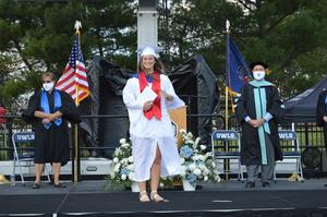 Graduate in white gown poses after receiving her diploma