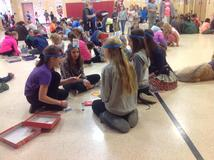 A group of female students with headbands playing a boardgame. One student has a working dog sitting beside her.