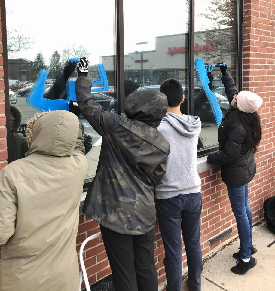 The backs of four students as they decorate a window