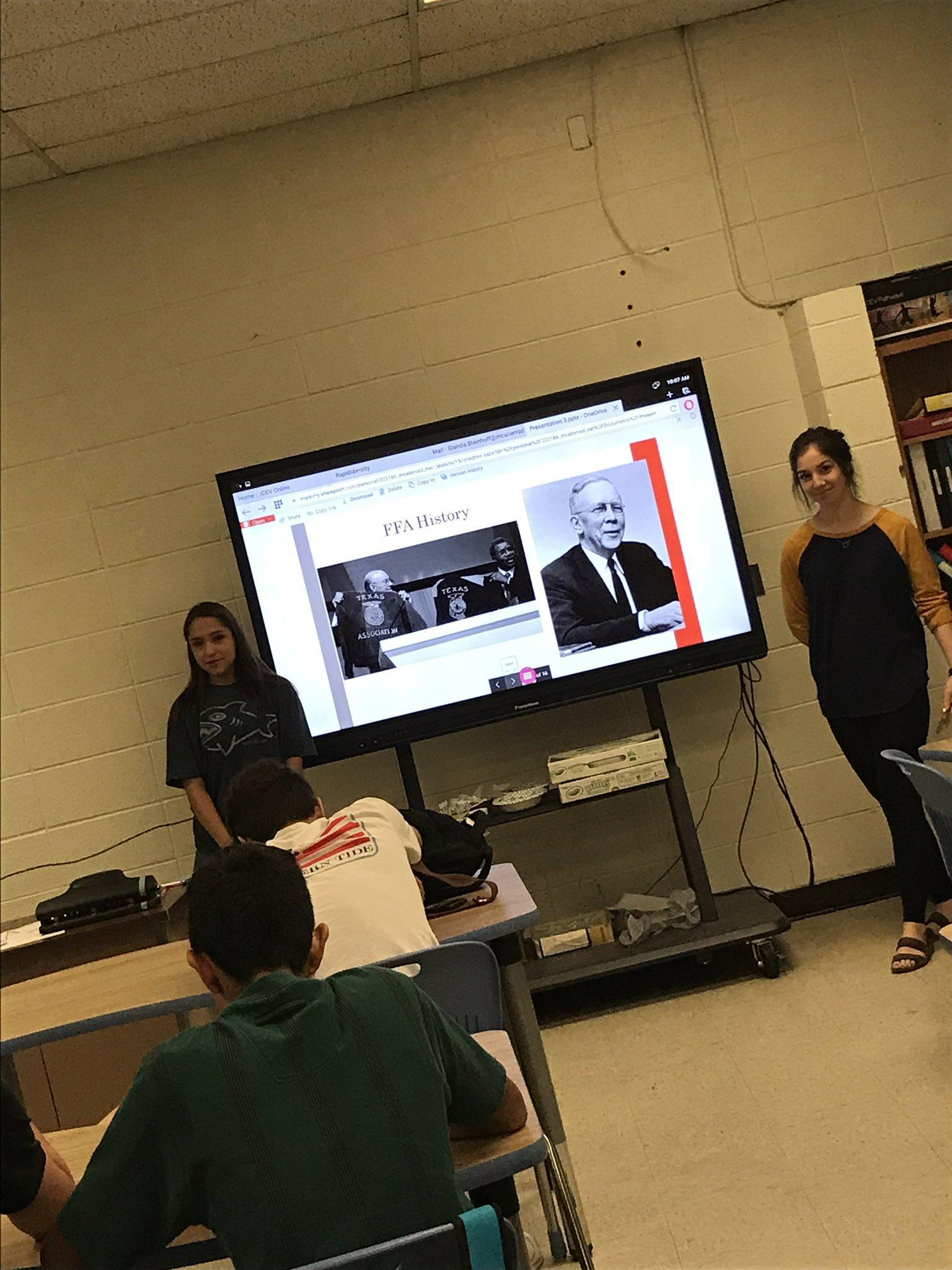 student presenting in front of classroom
