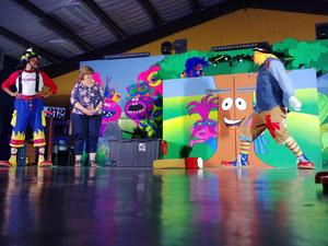 Image of two clowns and a teacher standing in front of colorful stage.