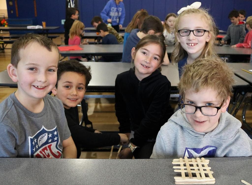 Photo of four Tamaques 2nd graders smiling as they participate in design challenge during STEAM Day.