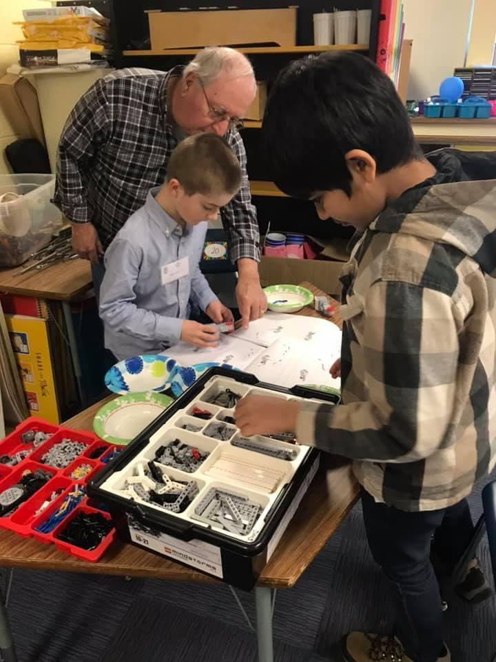 children working with an adult on robotics project