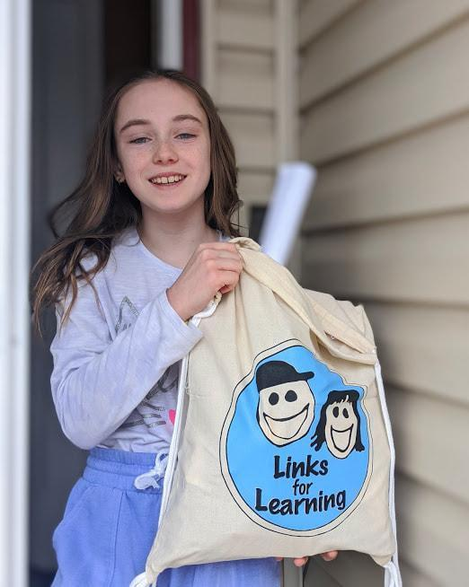 Smiling girl carrying supplies for a project