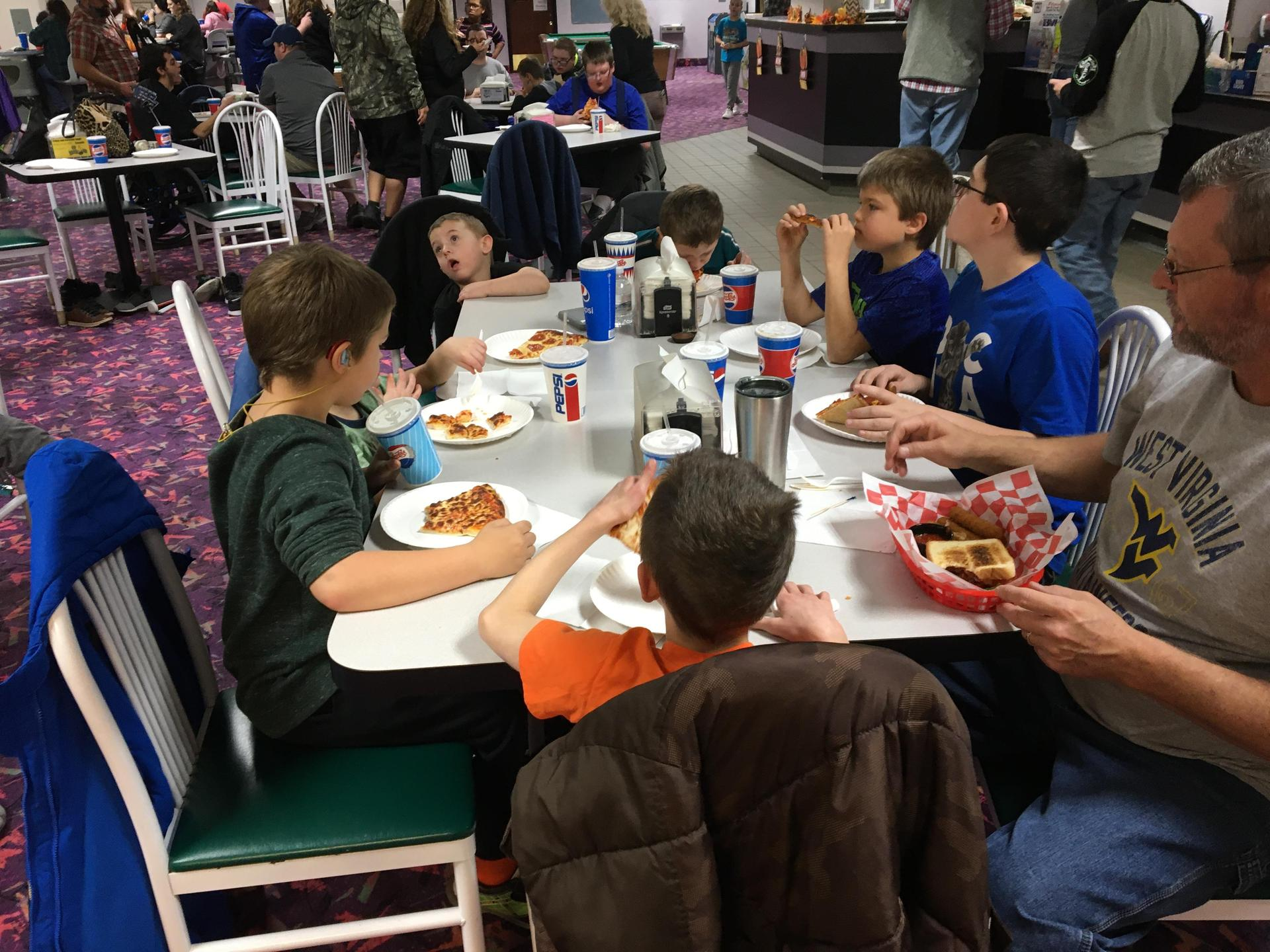 Students sitting around a table for dinner at the Bowling Alley