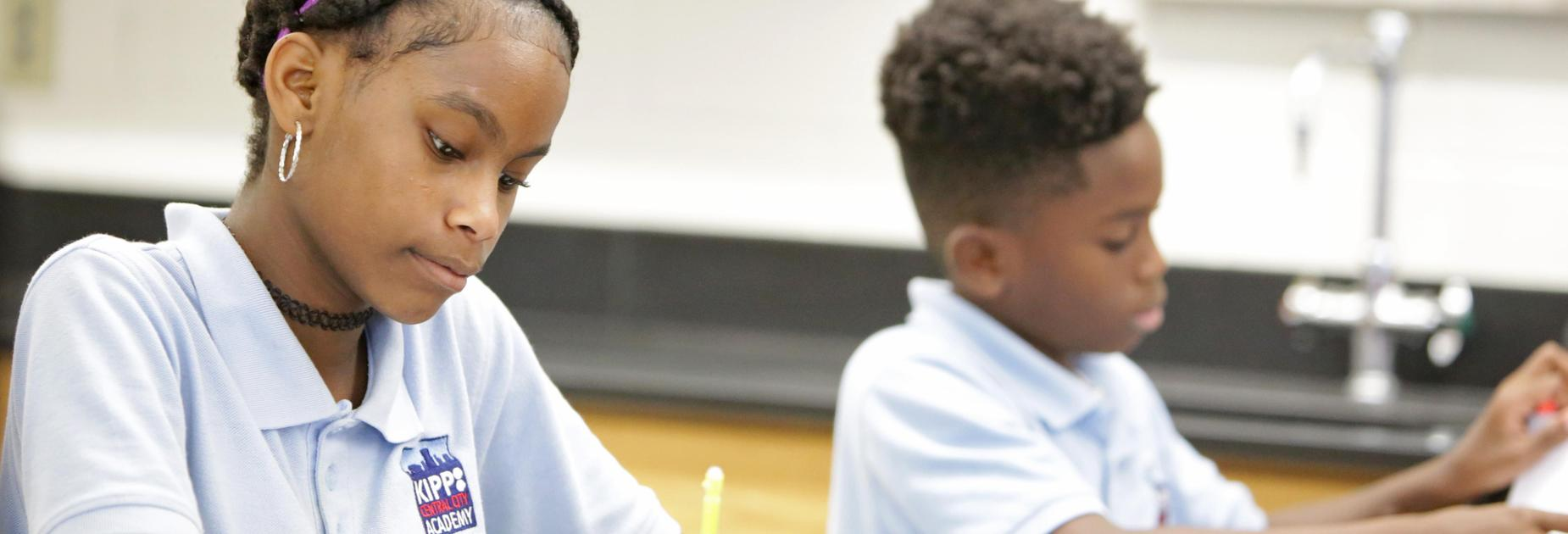 a female and male KCCA student working at a desk in a science lab