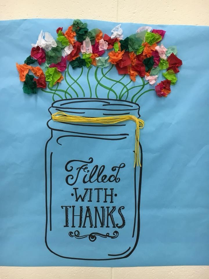 Picture of a flower filled jar that says 'filled with thanks'