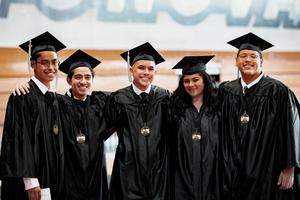 Five Del Mar High graduates pose in their cap and gown