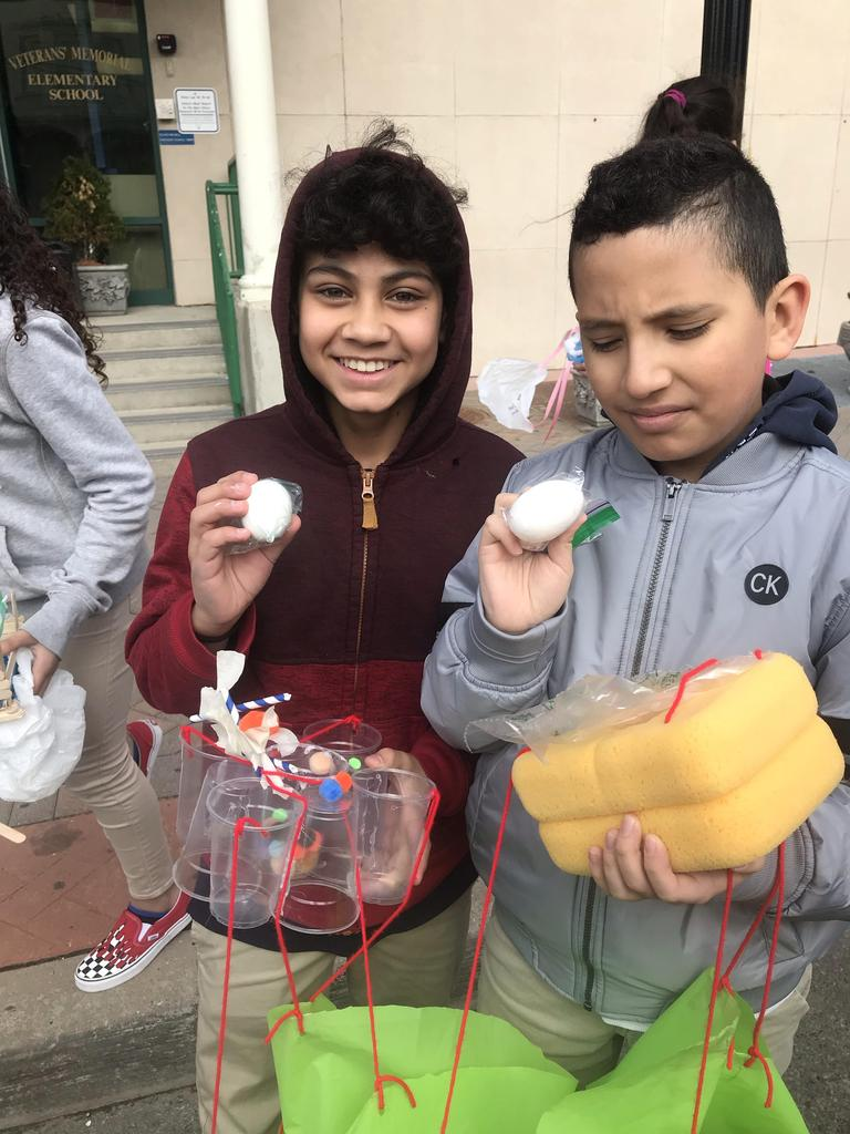 two boys proudly holding their safe eggs from the drop with the container the eggs where dropped with