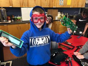 3rd Grade student holding technology pieces