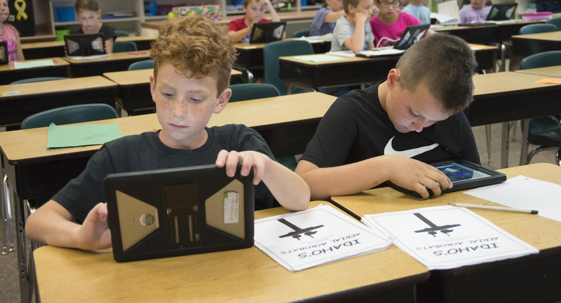 Two boys work on their iPads