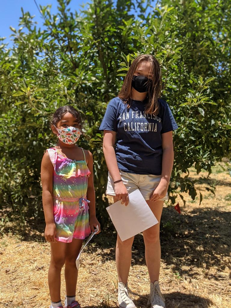 8th grader and Kinder Student standing in front of tree
