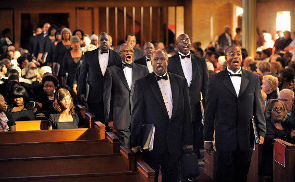 A photo of Heritage Choral Ensemble marching down a church aisle to sing a concert of Negro Spirituals