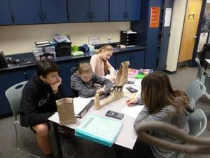 TKMS math students work together to determine the number of candy pieces and the number of gum pieces in each bag.