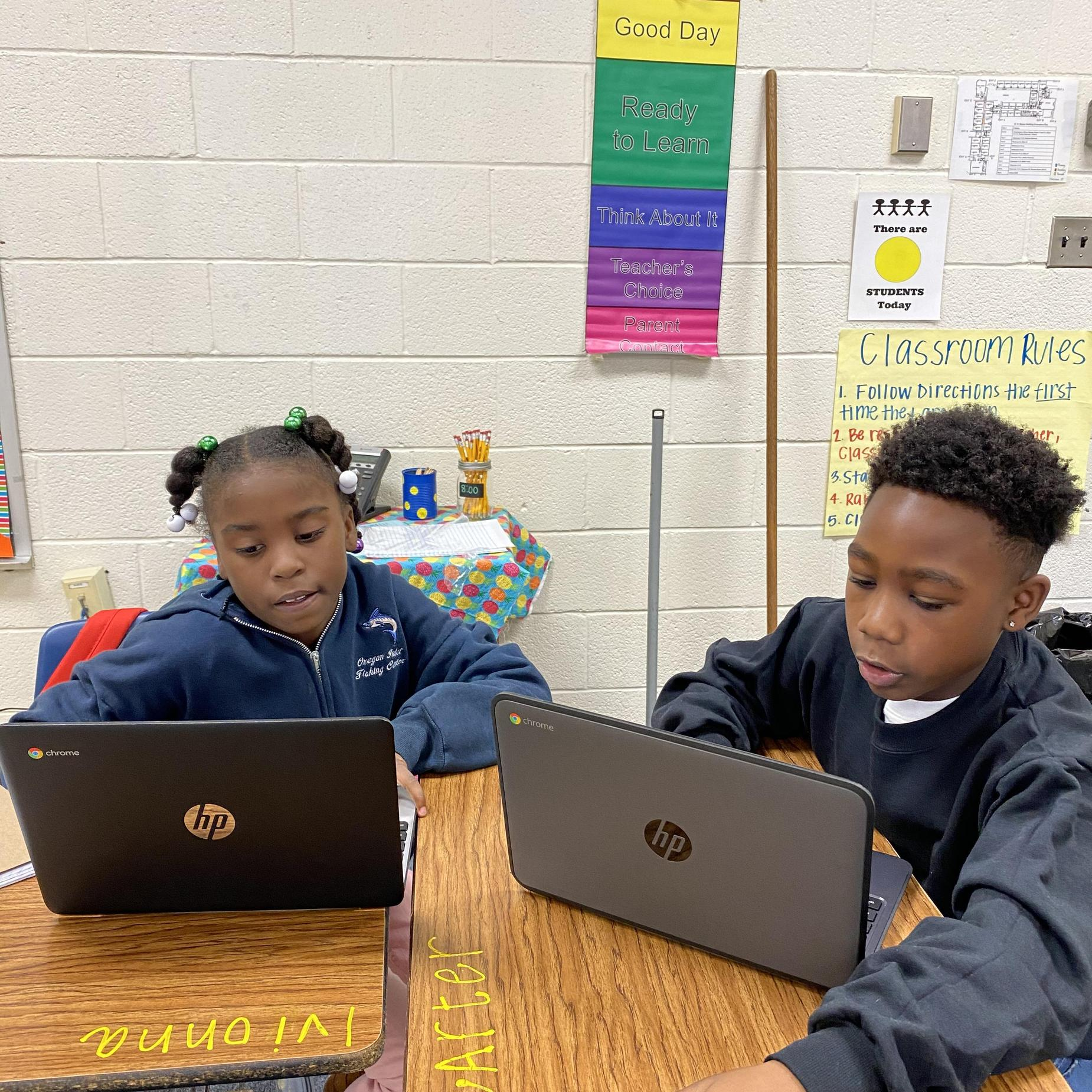 Two students on their chrome books.