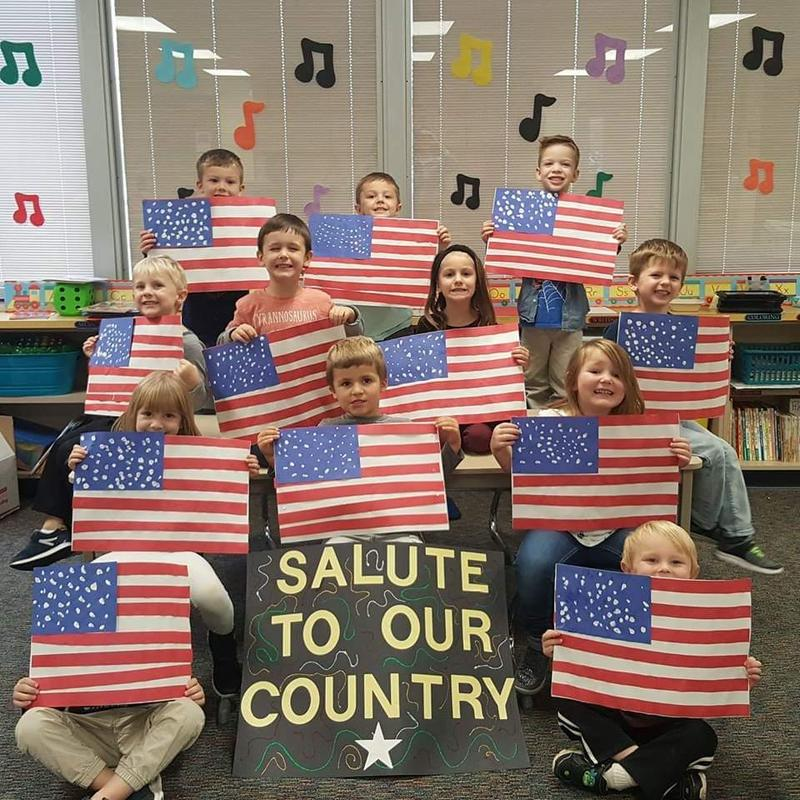 students hold up american flags they made in class.