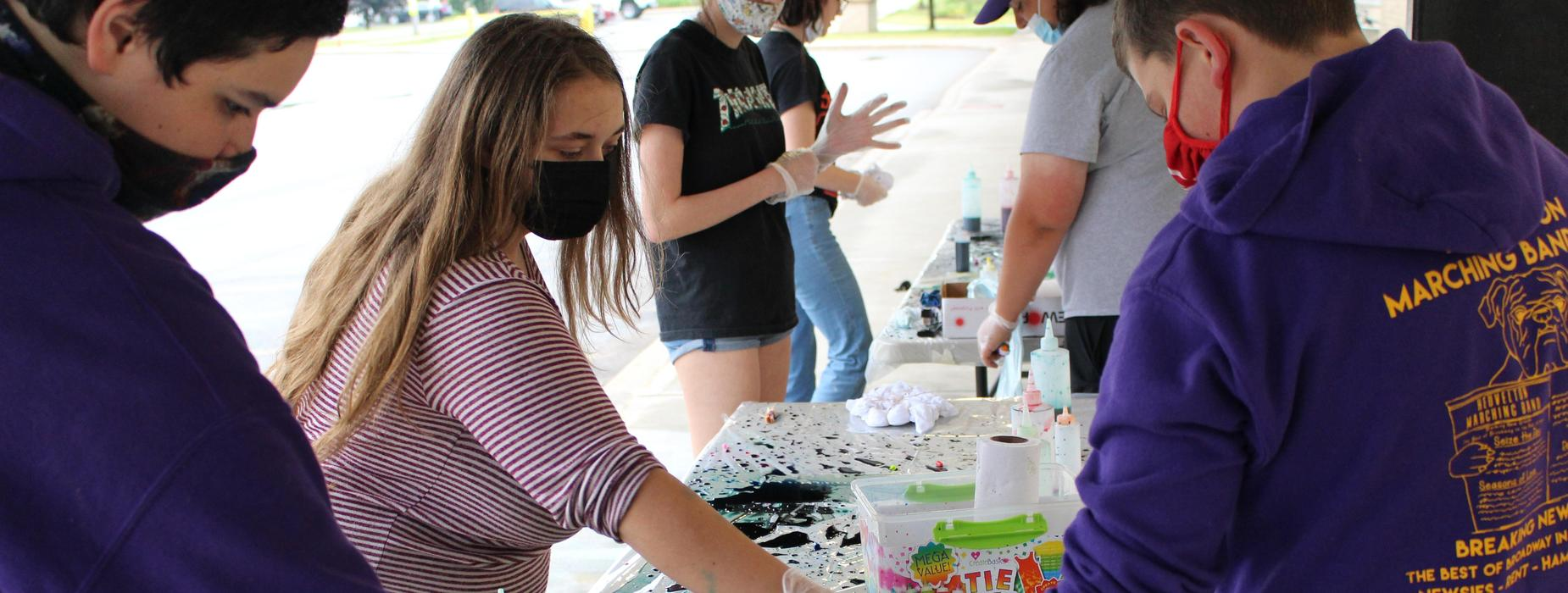 High school students tie dying shirts