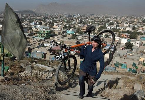 Shannon Galpin carrying her bicycle up stairs in Afghan village