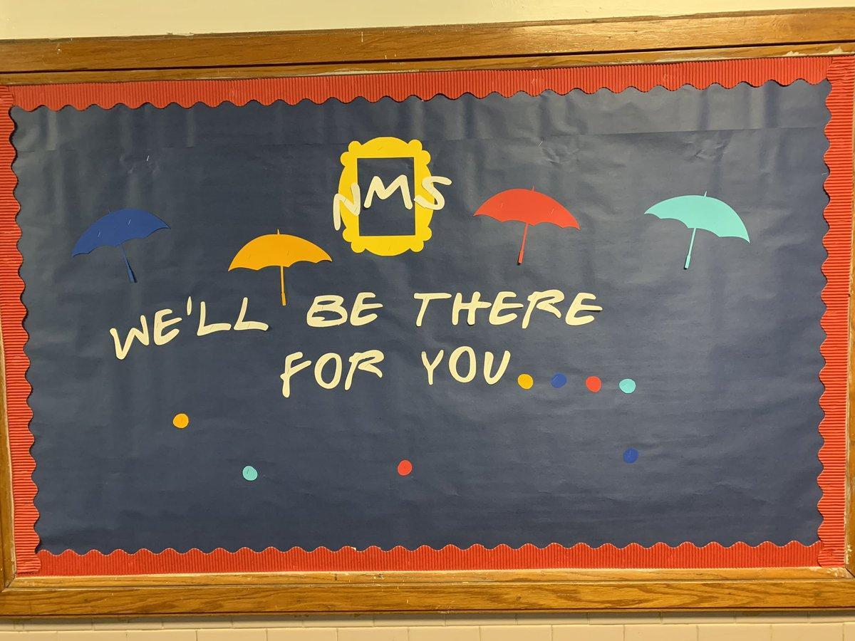 NMS bulletin board with pictures of umbrellas with a caption of We'll be there for you...
