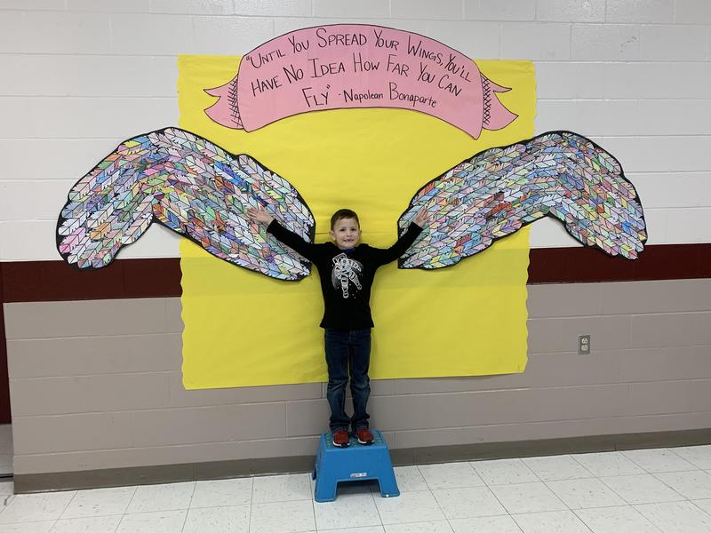 Student standing in the middle of drawing of wings