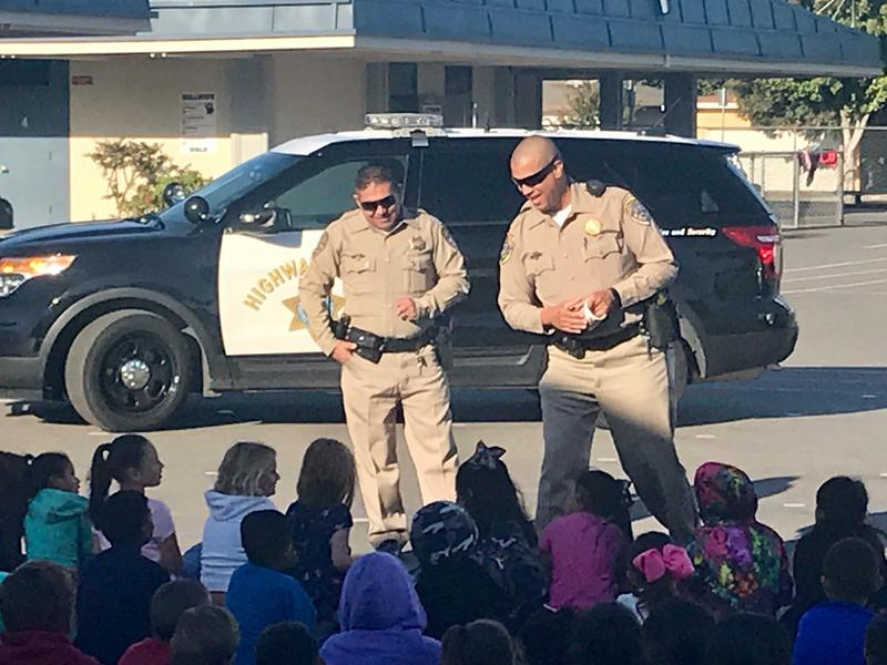 2 CHP officers standing in front of a CHP vehicle presenting to young students
