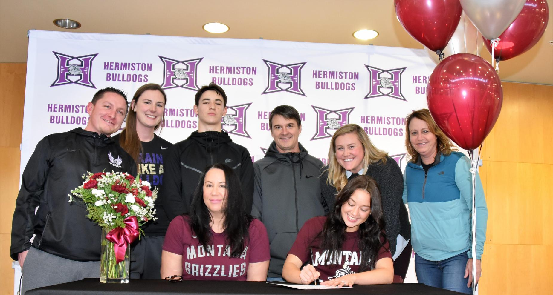 Female student is surrounded by coaches as she is signing her letter of intent.