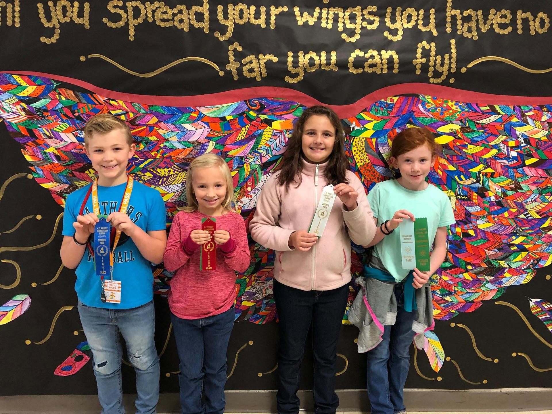 Four science winners hold up their ribbons.