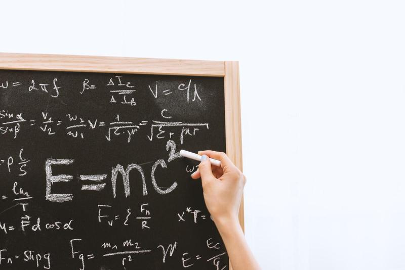 Picture of hand writing a math problem on chalkboard.
