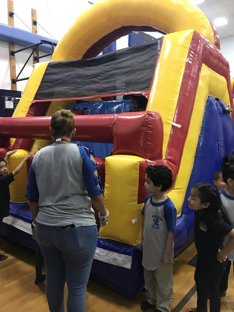 blow up bouncy house with students waiting to get on