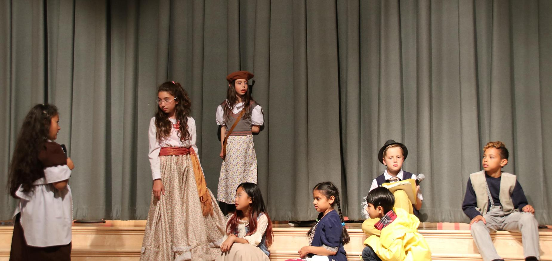 Students on stage performing The Adventures of Pinocchio