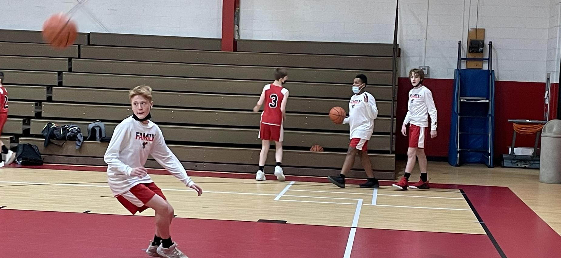 Basketball players practice in a gym.
