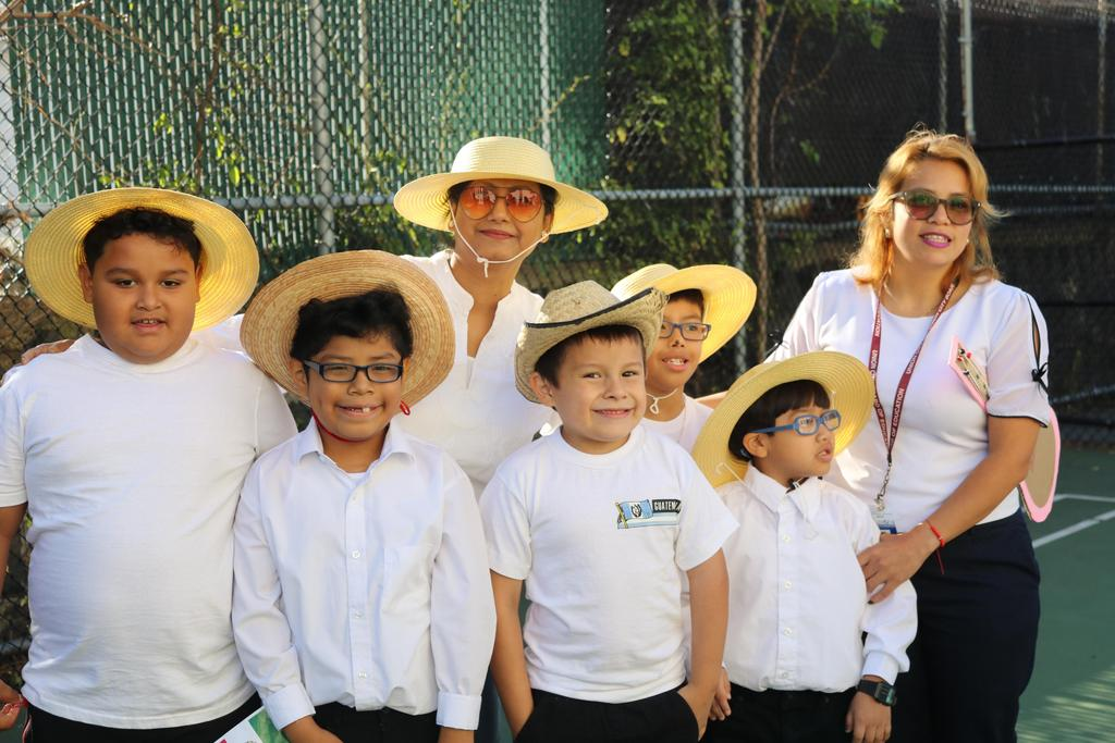 a group of boys wearing straw hats with two teacher aide in the school yard