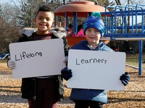 lifelong learners signs in front of two boys on playground