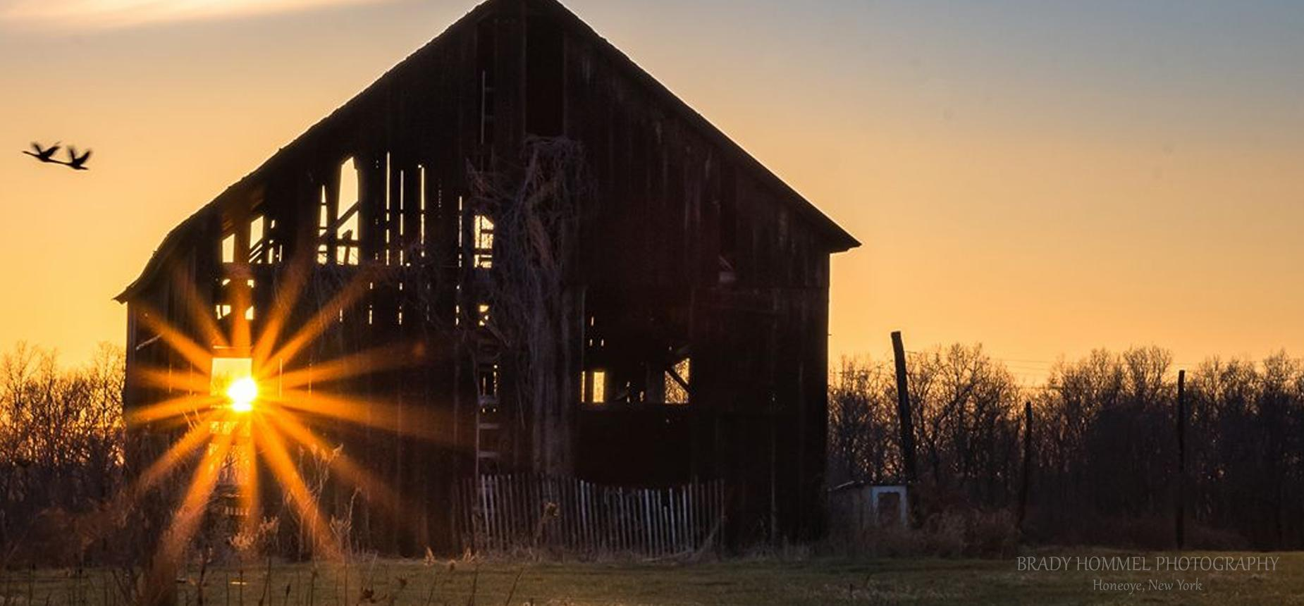Photograph of the sun shining through a barn at sunset by Bradey Hommell.