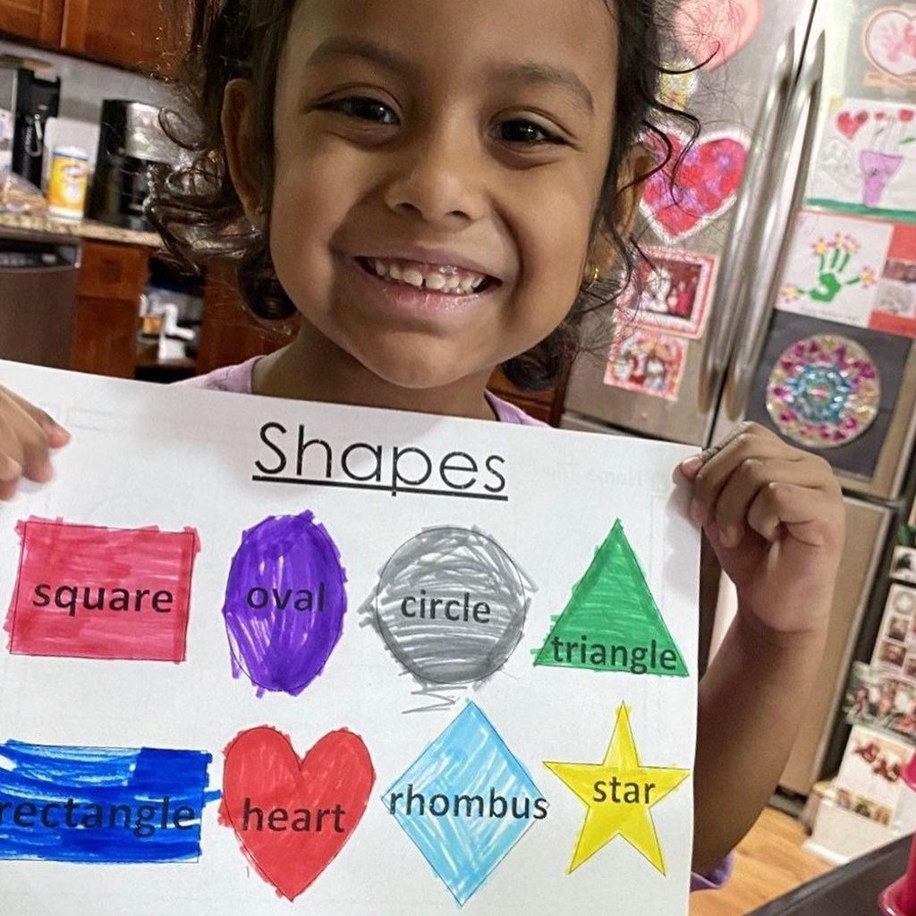 little girl in her kitchen holding up her colored shapes activity