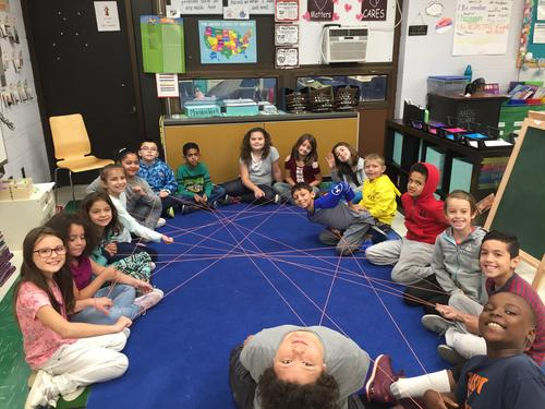 students sitting in a circle holding string to make a spider web