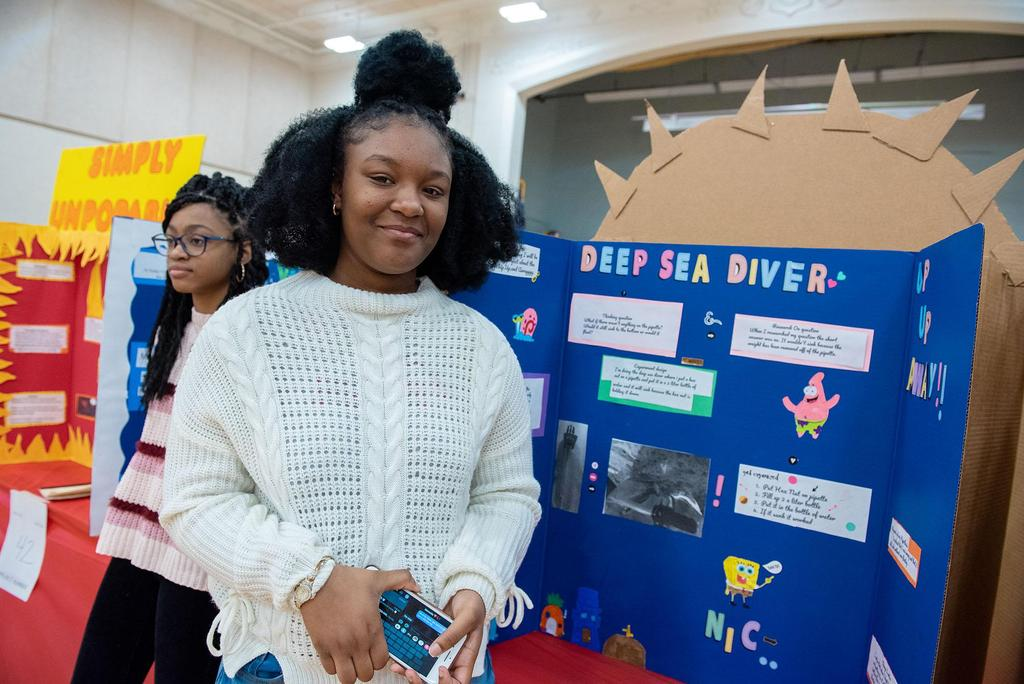 A student stands in front of her project called Deep Sea Diver