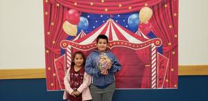Students posing with the Math Night backdrop