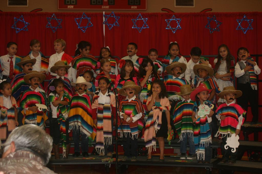 Young Children on Stage wearing ponchos.
