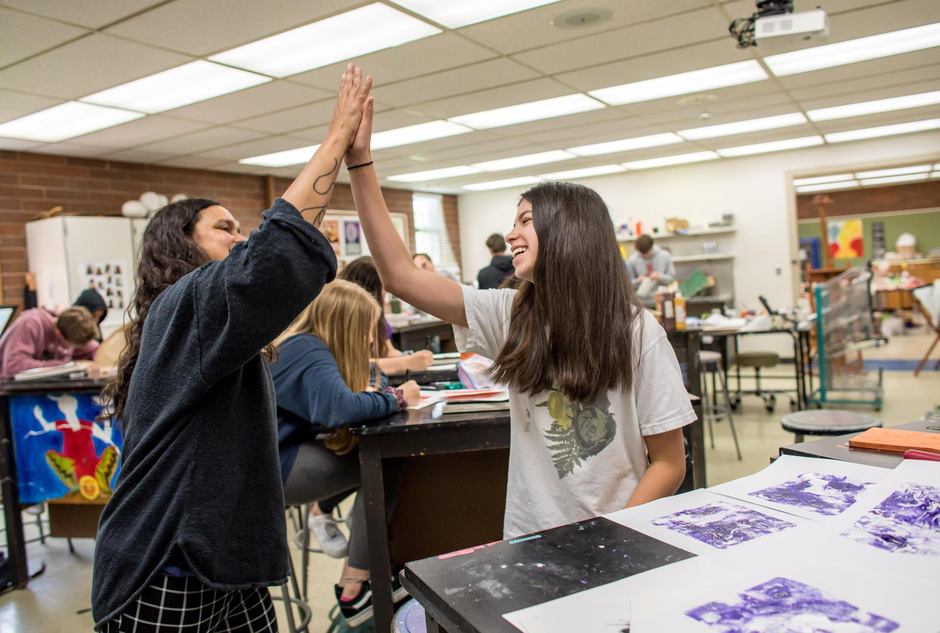 teacher high-fiving a student