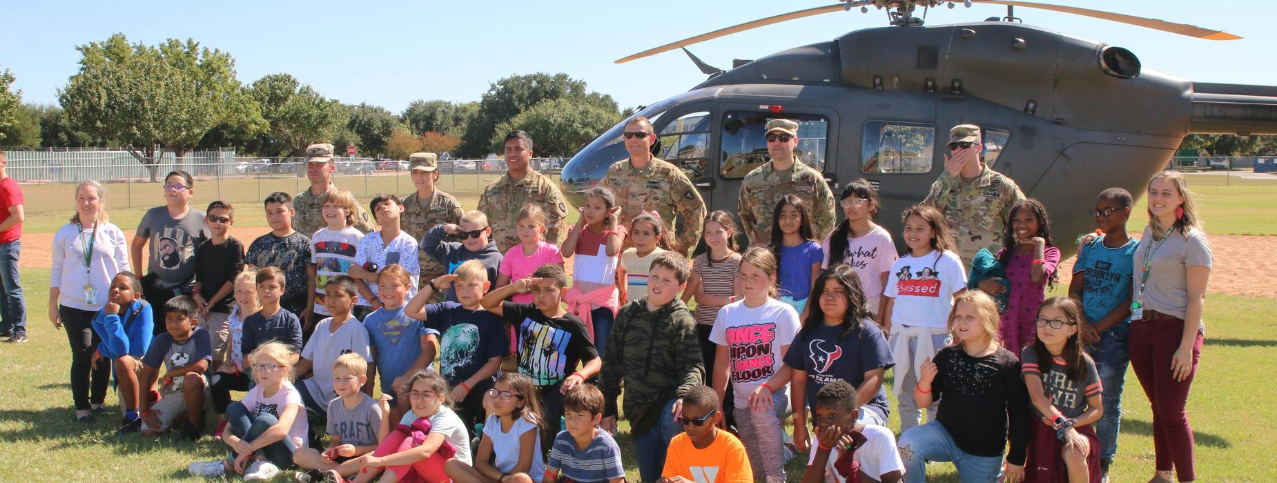 Students in front of helicopter