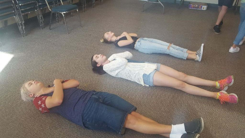 Picture of students lying down on the ground after playing a mystery game