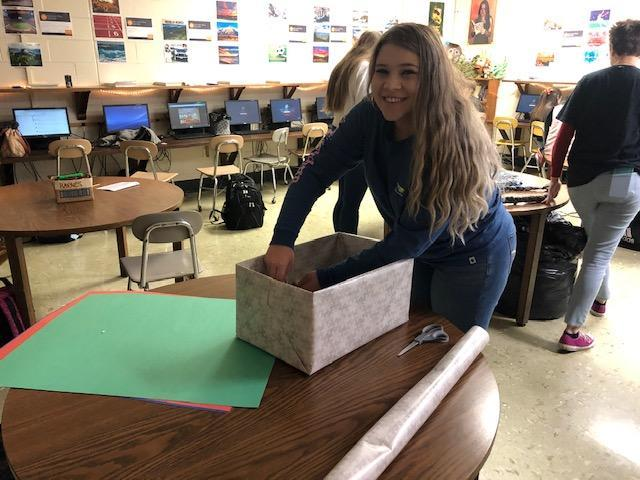 Making a box for homeless shelter donations.