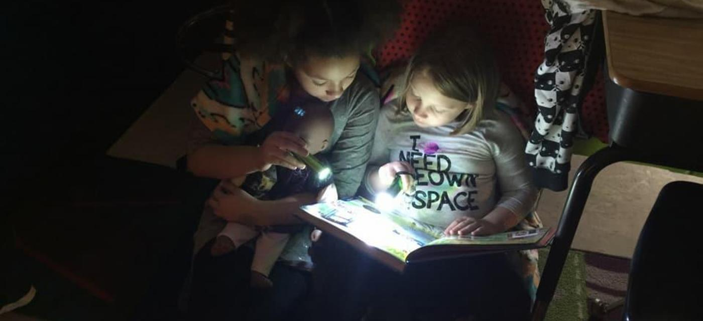Students reading by flashlight.