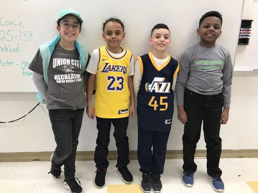 four kids wearing their jerseys