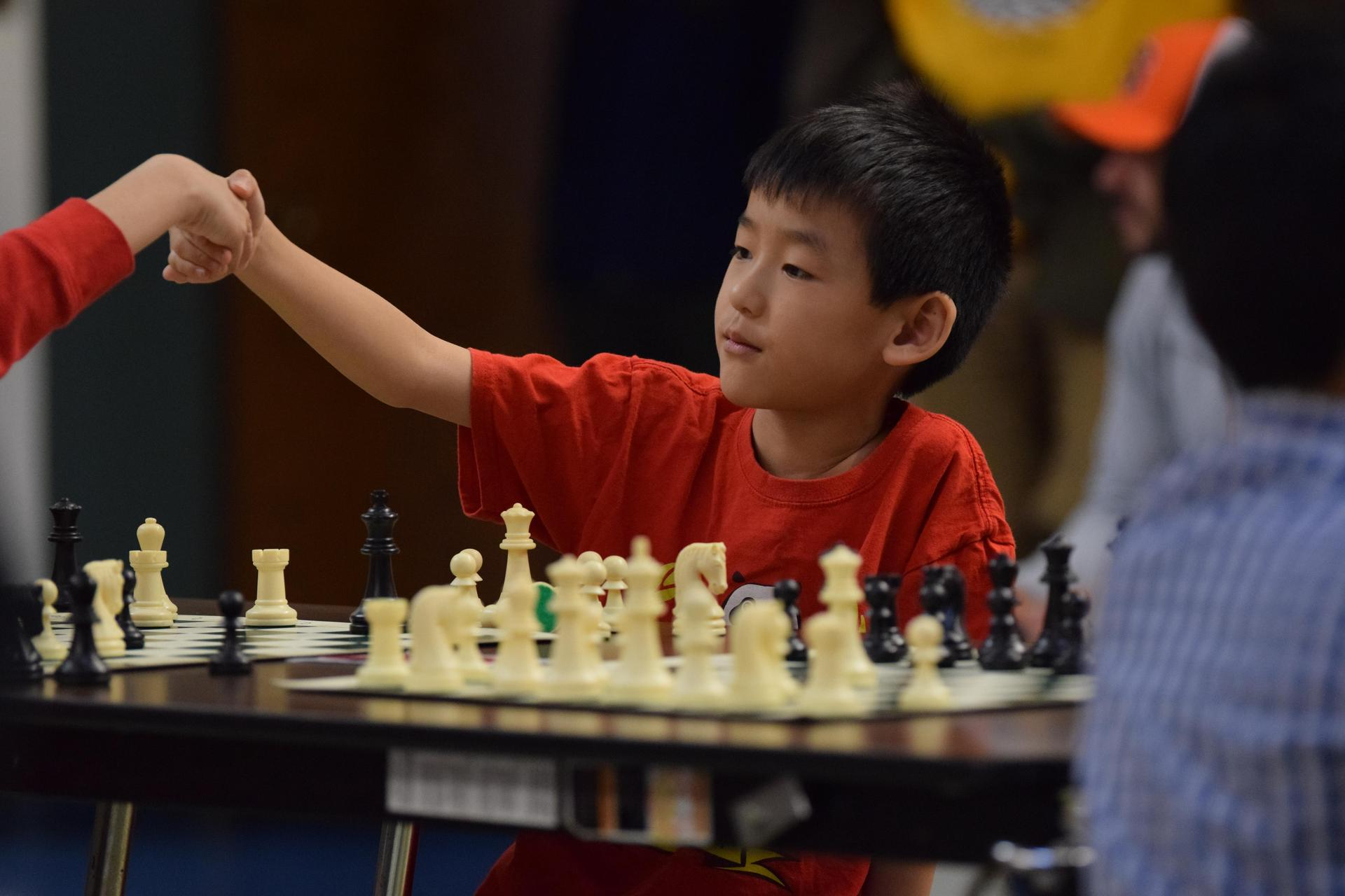 young boy shaking chess opponent's hand
