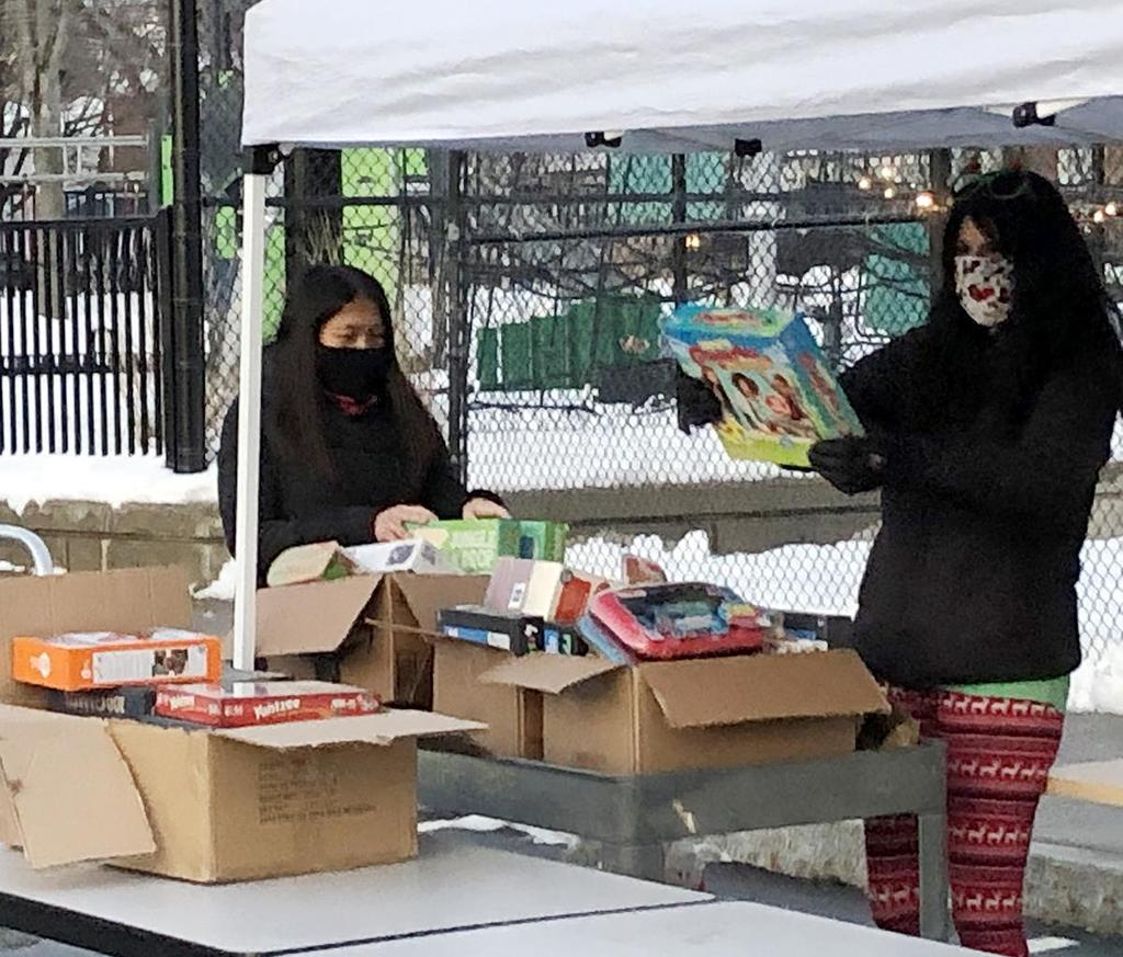 Two women sort through boxes of new gifts
