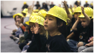 A gym full of Shiloh Hills K-6 students wearing yellow hard hats listening attentively to invited speakers.