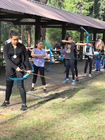 students shooting bows and arrows