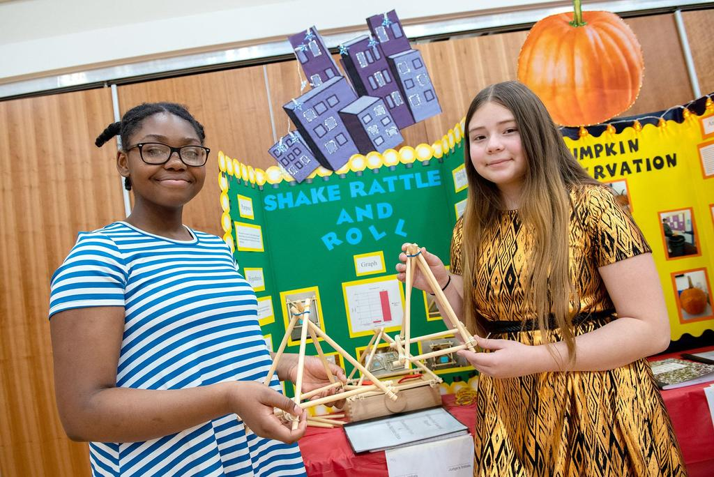 Two students hold models made out of long and thin pieces of wood